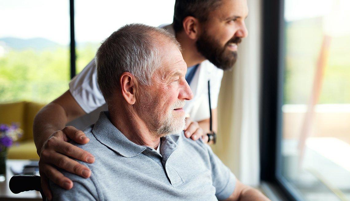 Un hombre en un hogar de ancianos sentado en una silla de ruedas y mirando por la ventana junto a un trabajador de enfermería.
