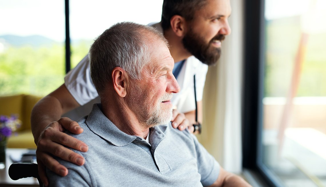 A man in a nursing home sitting in a wheel chair and looking out the window next to a male nursing homer worker