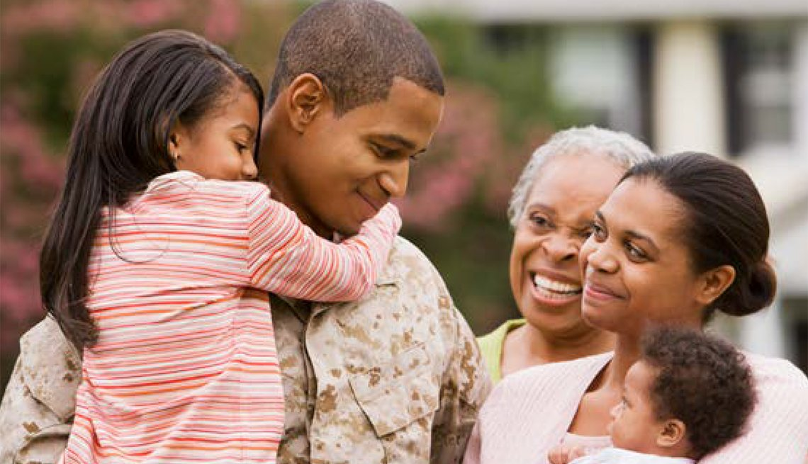 Man in a military uniform holding his daughter and smiling at his mother, wife and baby