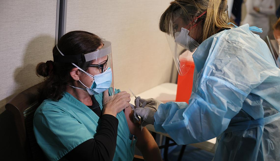 Una trabajadora de un hogar de ancianos con una mascarilla recibe una vacuna covid en el brazo.