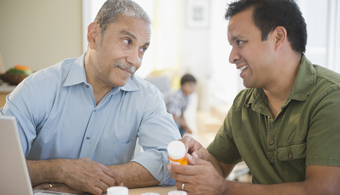 A man holding a prescription pill bottle explaining the medication to his father