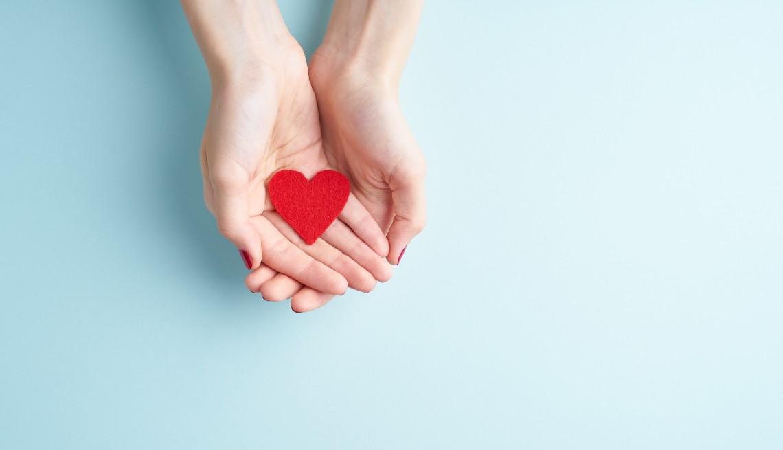 Una persona sosteniendo un corazón rojo en las manos.