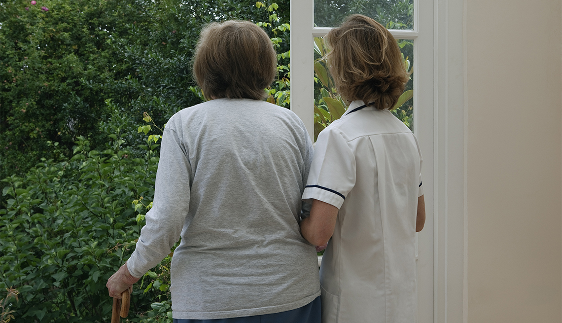 woman being assisted by a nurse at an assisted living facility