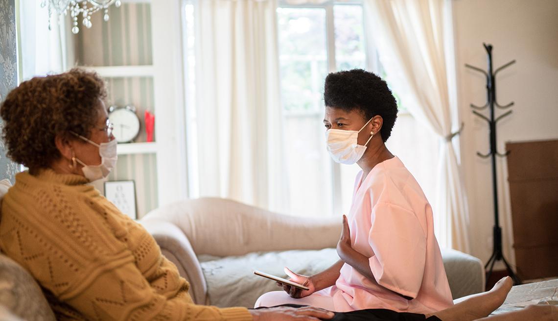 Una doula de la muerte con una máscara facial hablando con su paciente mientras está acostada en la cama.