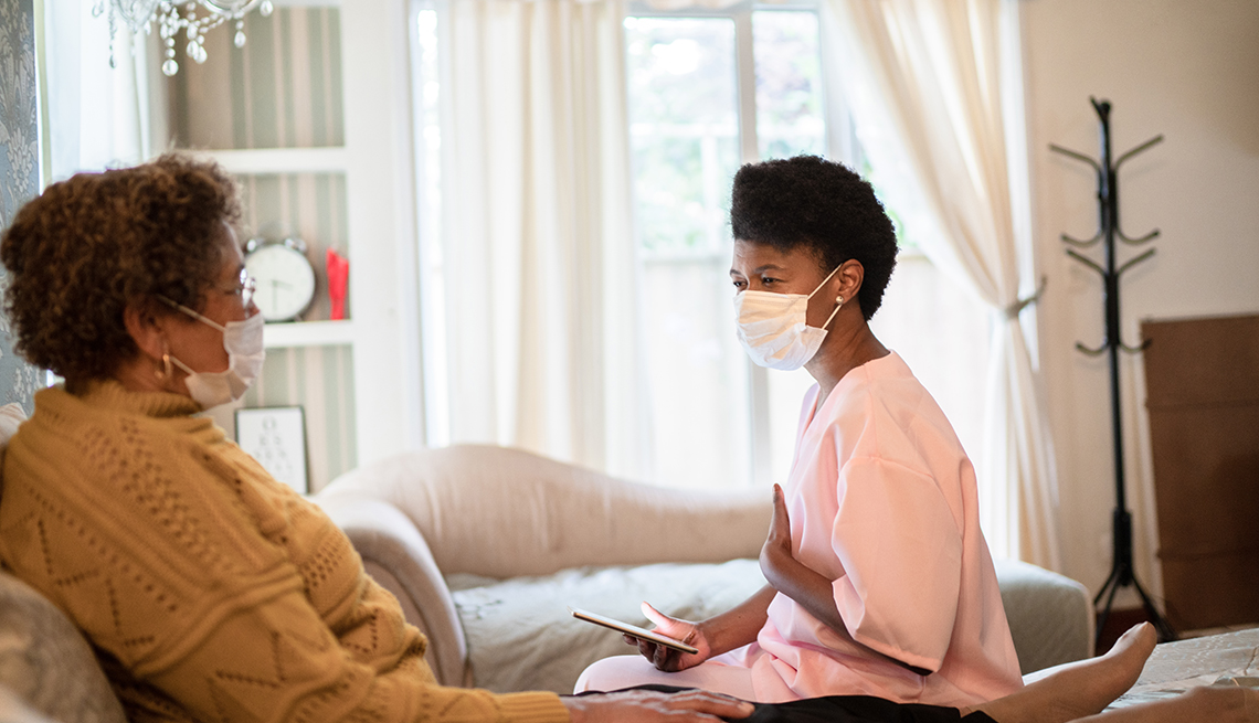 a death doula wearing a face mask talking to her patient as she lies in bed