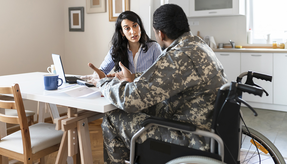 Un hombre con uniforme militar en silla de ruedas sentado en la mesa de la cocina.