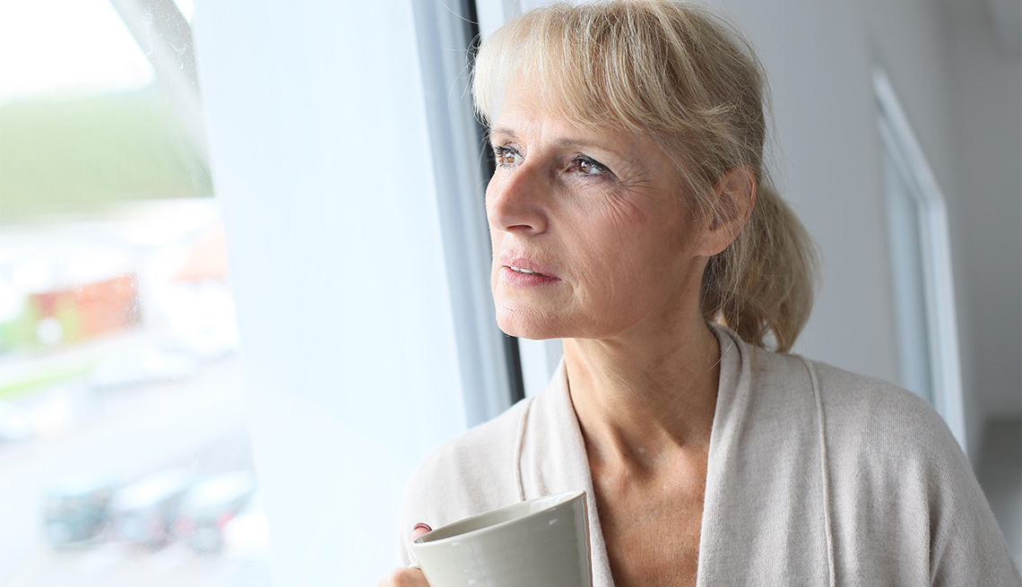 a lonely looking woman holding a coffee mug looking out a window
