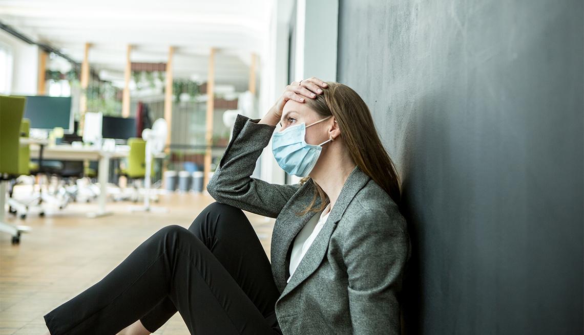 Mujer con máscara protectora facial luciendo preocupada en la oficina.