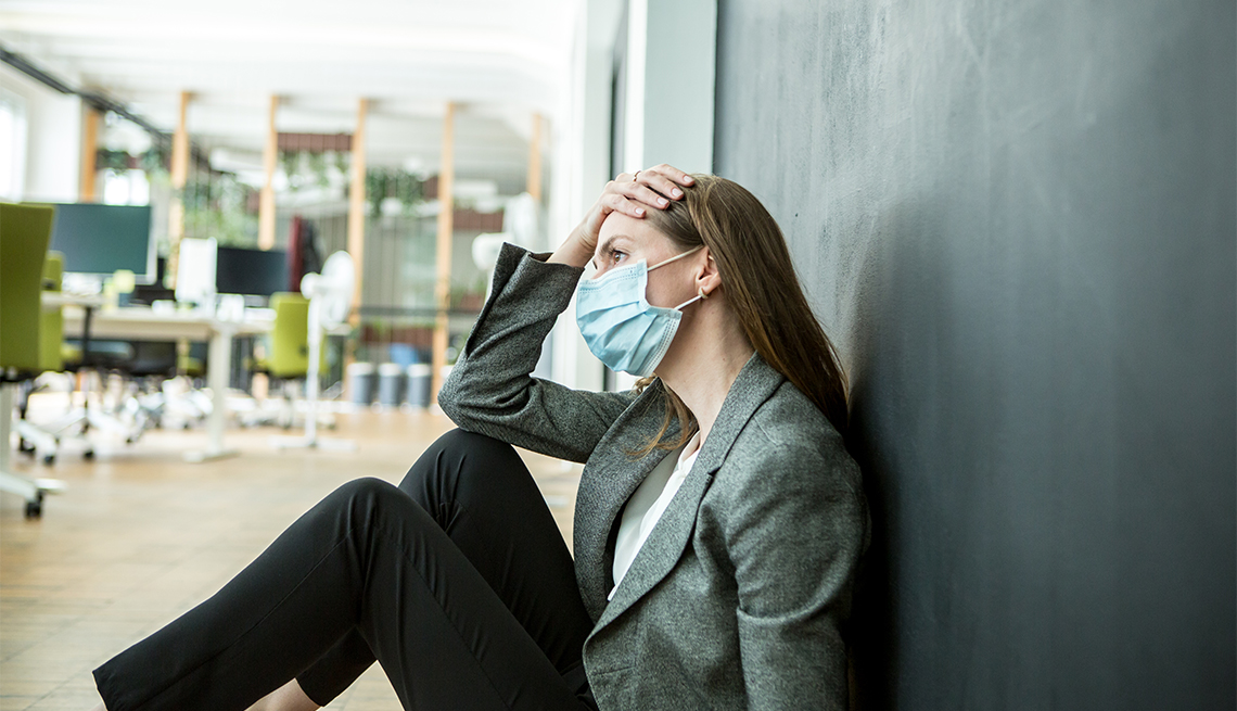 woman wearing a face mask sitting on the floor of her office with her hand on her head looking stressed