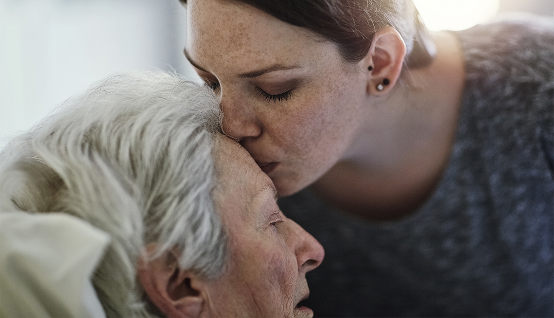 a woman kissing her mother on the forehead
