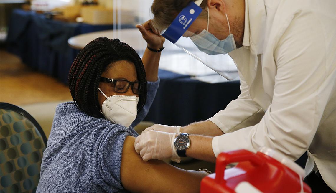Una trabajadora de un hogar de ancianos recibe su vacuna contra la COVID-19.