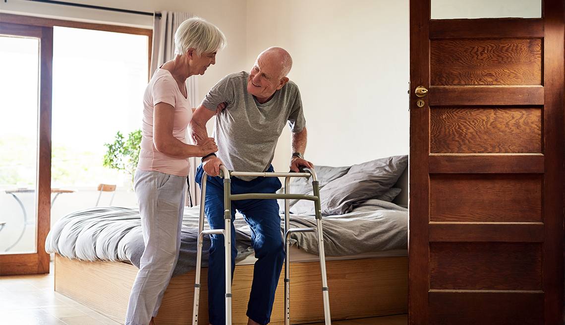 a woman helping her husband out of bed with his walker