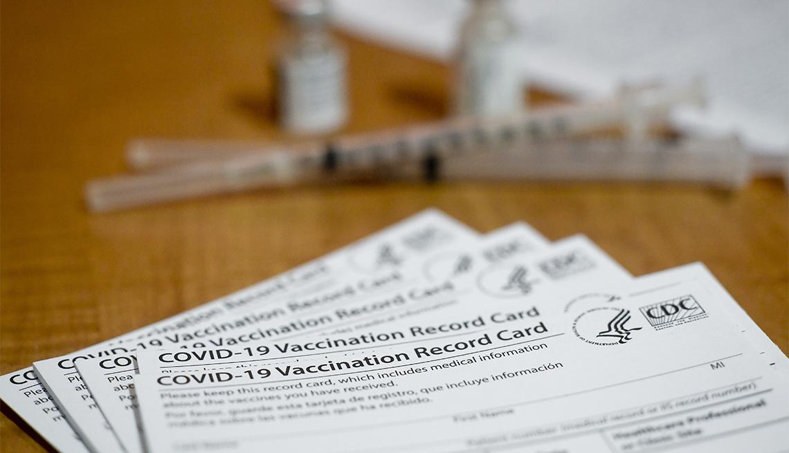 Una pila de tarjetas de registro de vacunación de la COVID-19.