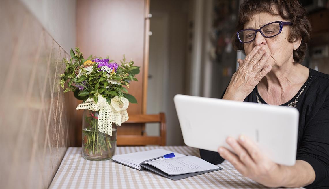 Una mujer sopla un beso mientras usa una tableta para una videollamada.