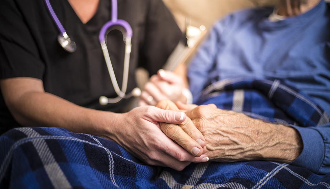 Una enfermera toma de la mano a un paciente.
