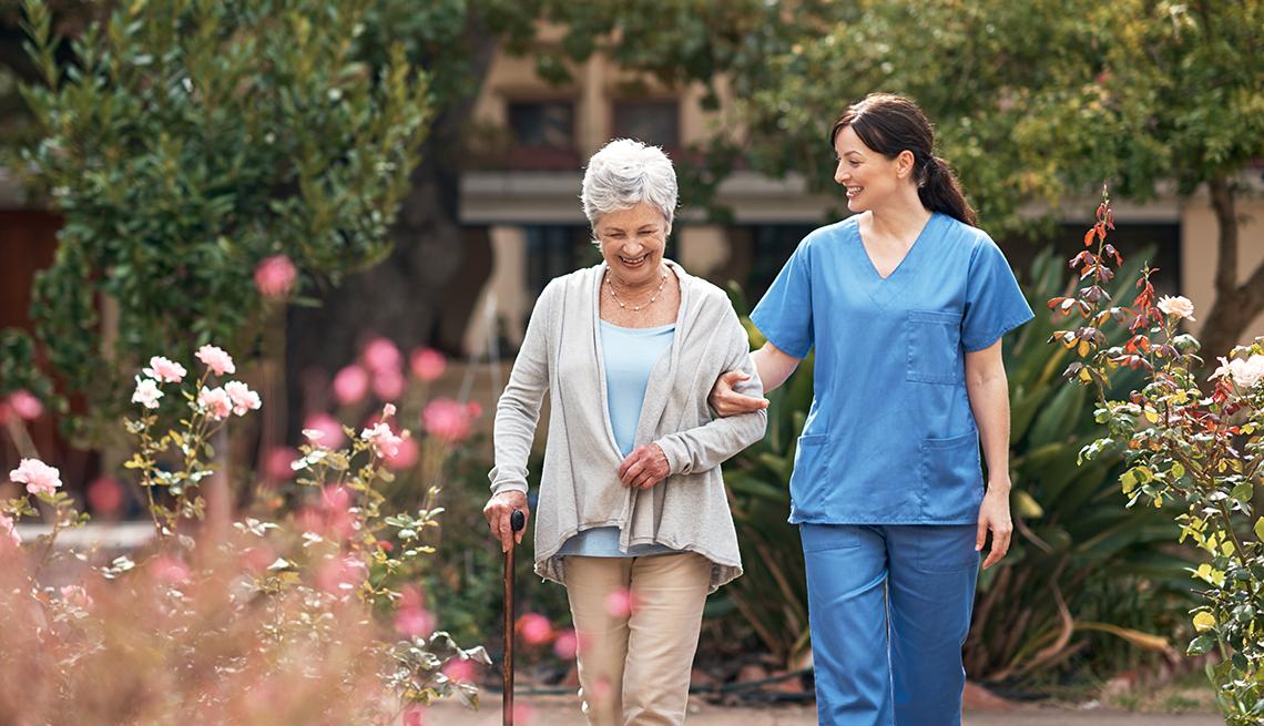 Una mujer y una enfermera caminando en un jardín.