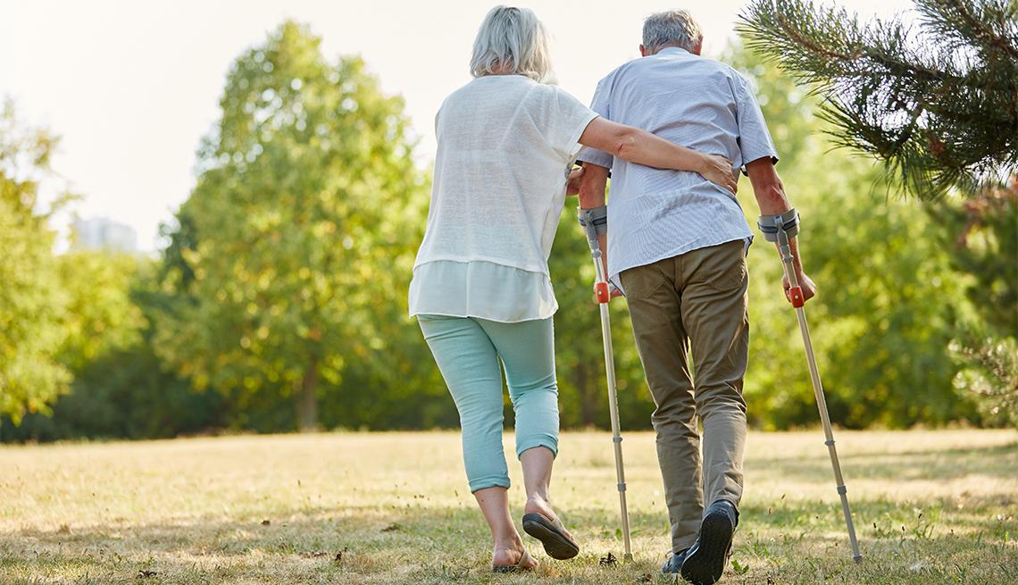 Cuidador ayuda a un hombre a caminar con muletas en un parque.