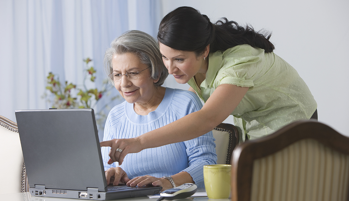 woman helping older woman with something on laptop