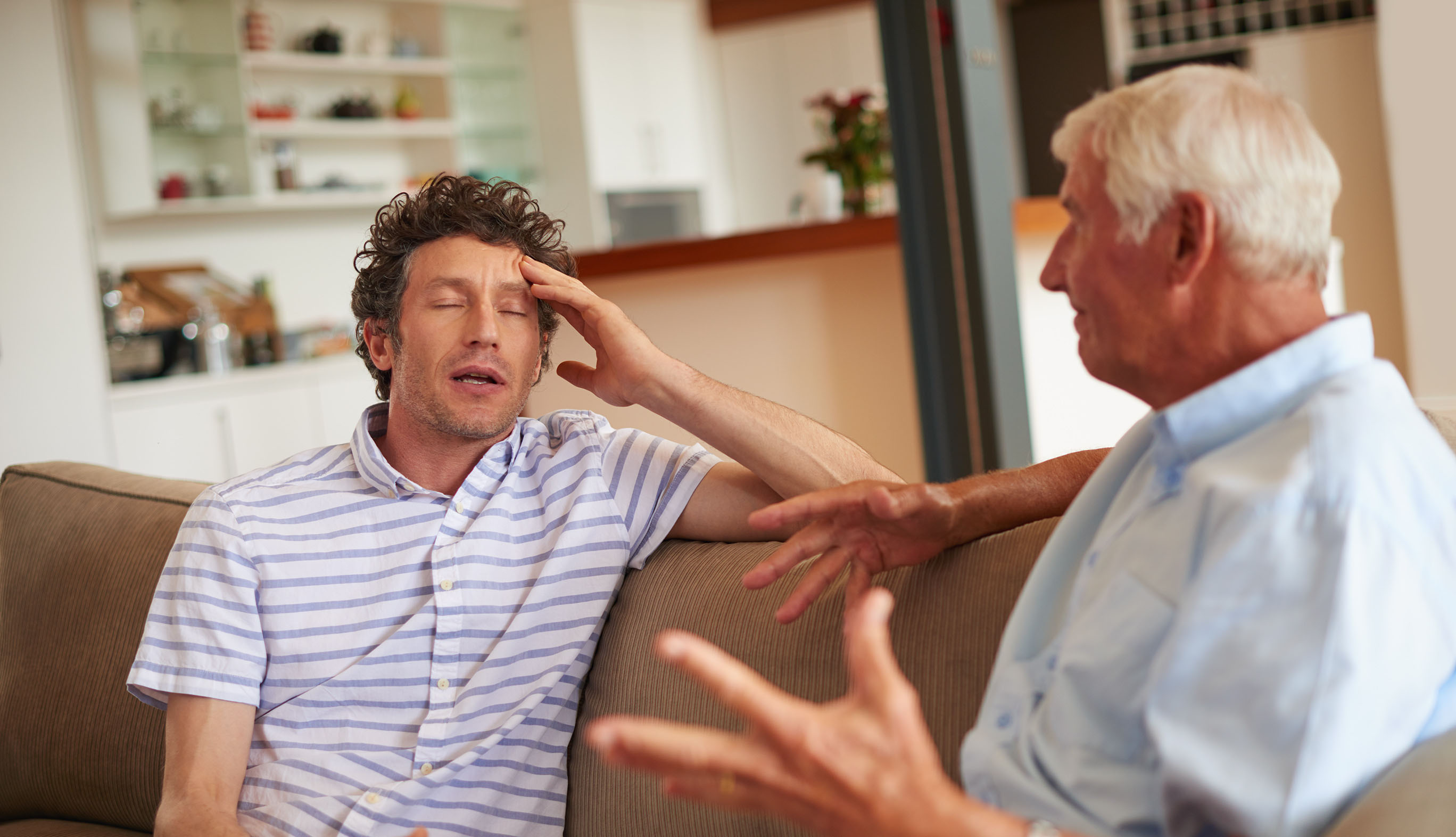 older man and son arguing on couch