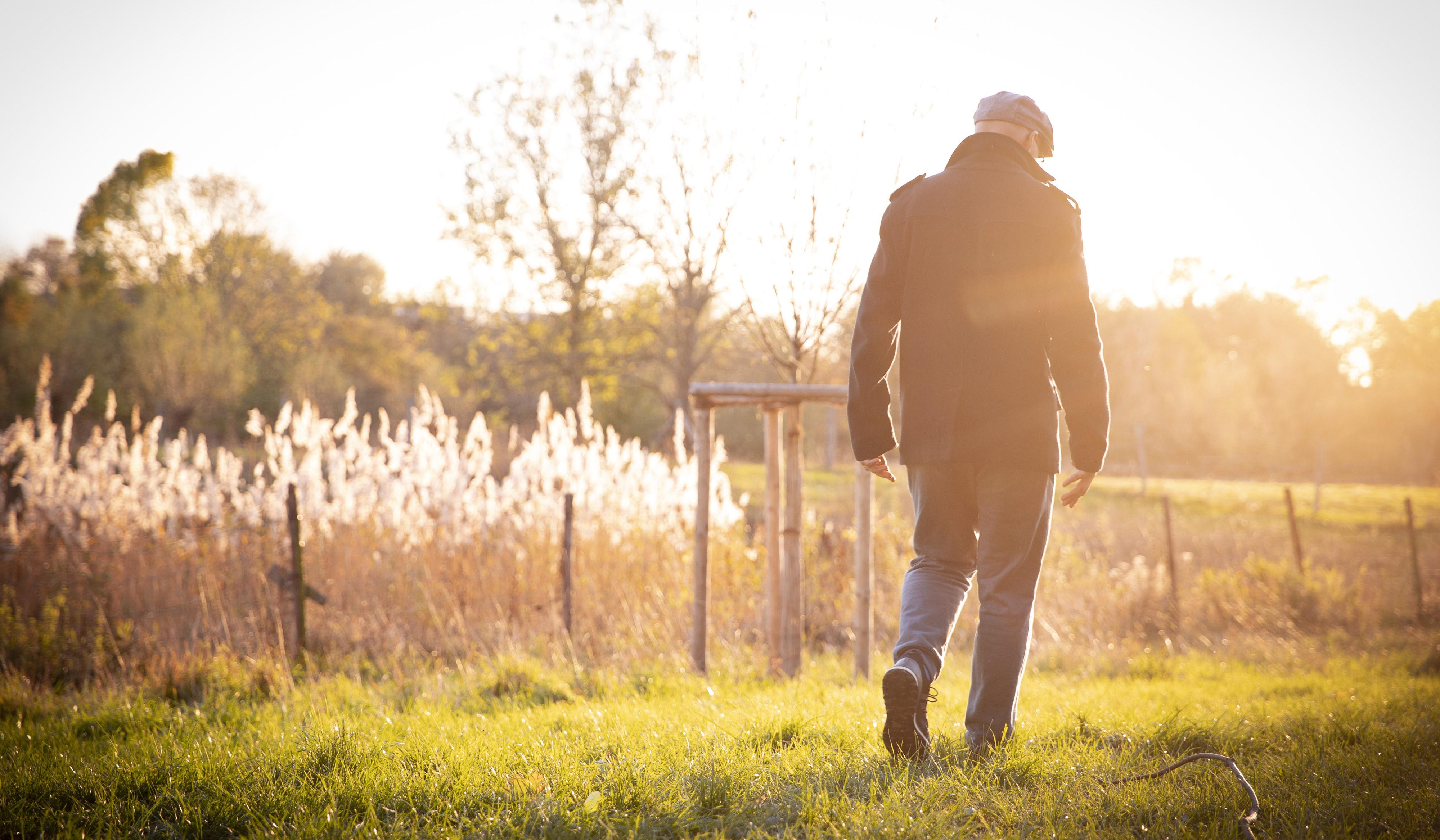 Un hombre mayor dando en un paseo otoñal.