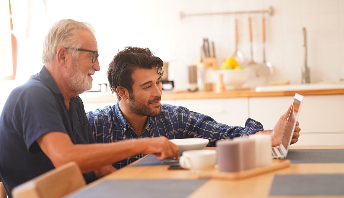 Un hijo adulto joven con un padre anciano se comunica con su familia en una videollamadas a través de una computadora portátil.