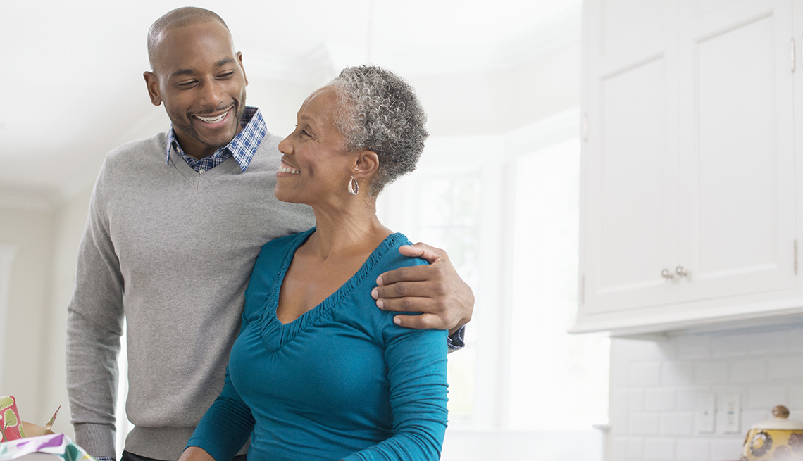 man with her arm around his mother in the kitchen