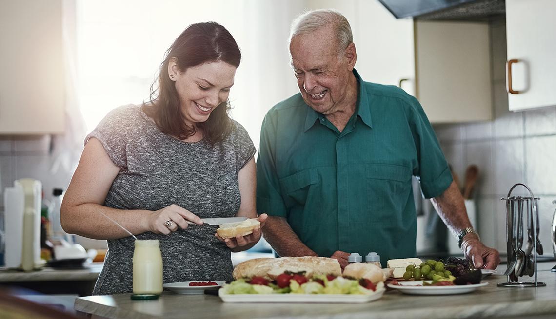 Shot of a woman making her senior parent a sandwich