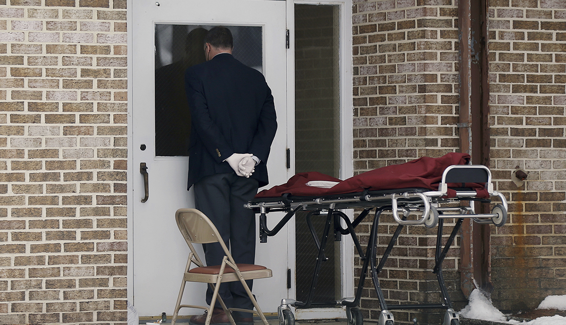 a funeral director standing next to an empty stretcher waits outside a nursing home door