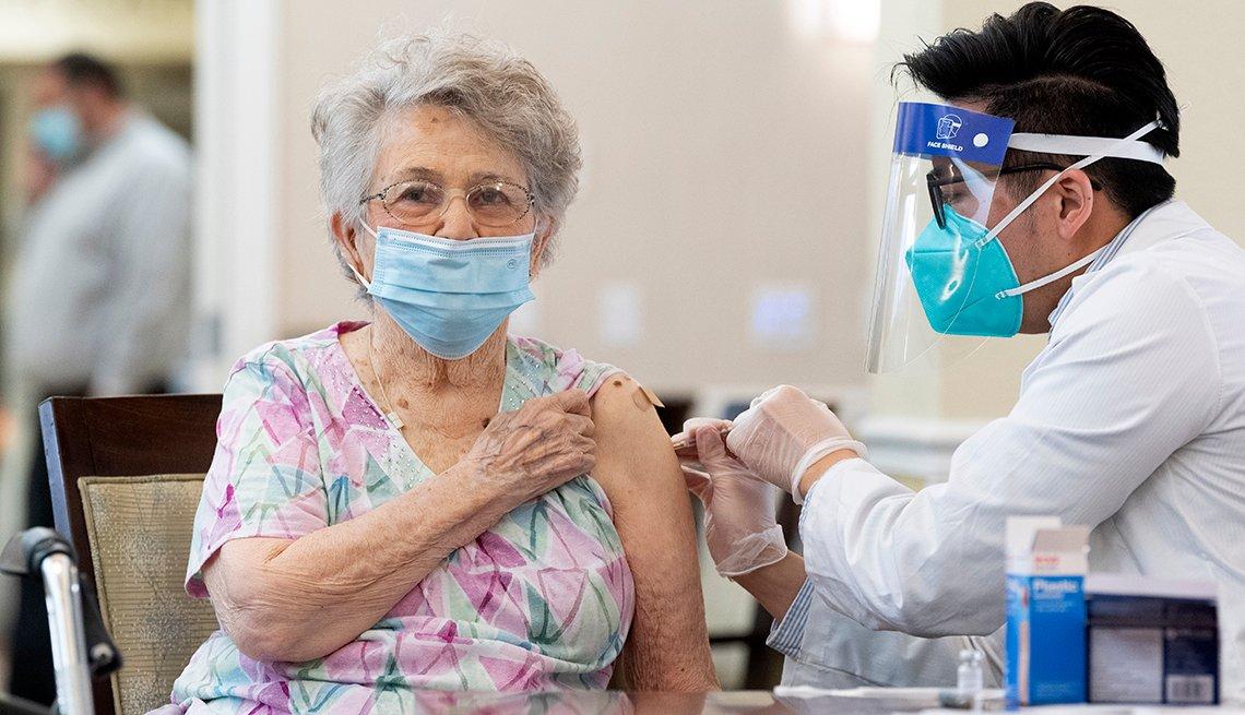 Un farmacéutico de CVS administra la vacuna Pfizer / BioNTech COVID-19 a un residente de la comunidad de ancianos de Emerald Court en Anaheim, California.