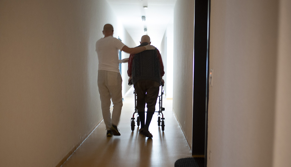 A male nurse helping a man using a walker walk down a nursing home hallway