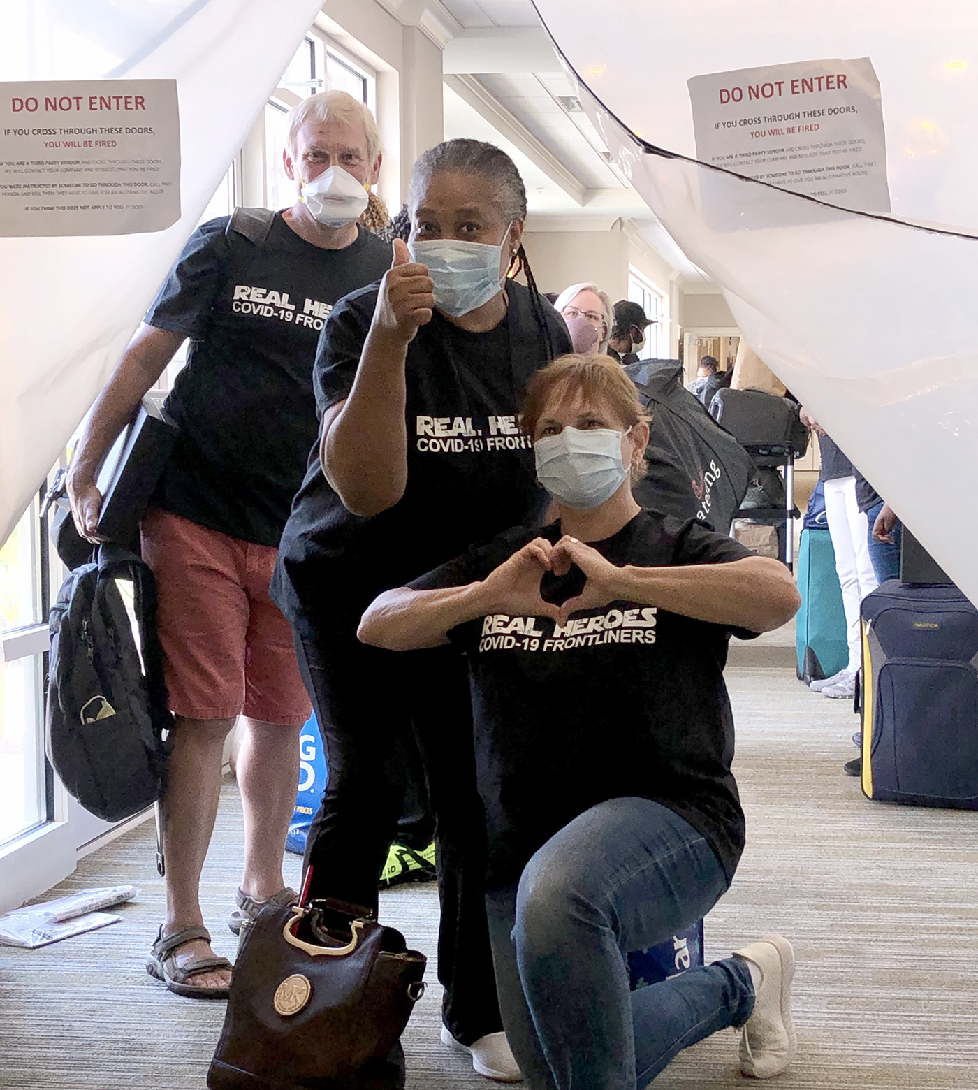 masked staff at a nursing home in front of zippered plastic sheeting wall