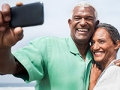 African American Seniors Smiling Together on Beach and take a video of themselves, Boomer couples