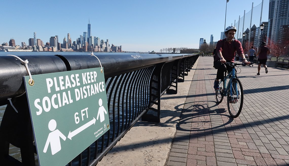 a lone bicycle rider cruises by a social distancing sign on the hudson river walkway in hoboken new jersey