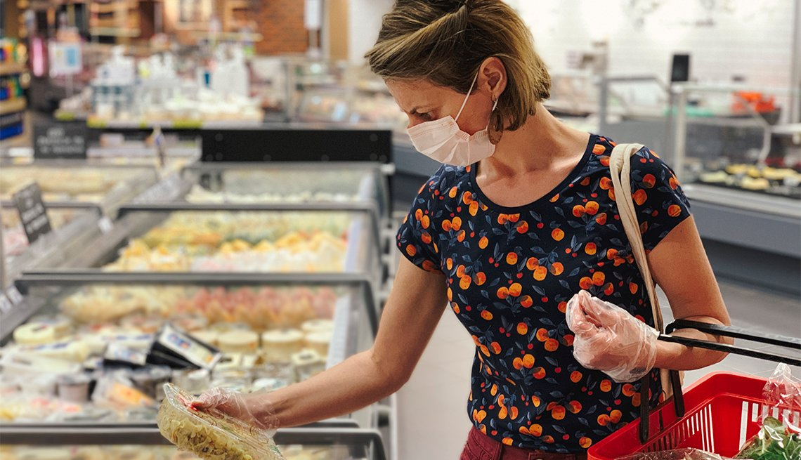 Woman wearing protective mask shops for groceries