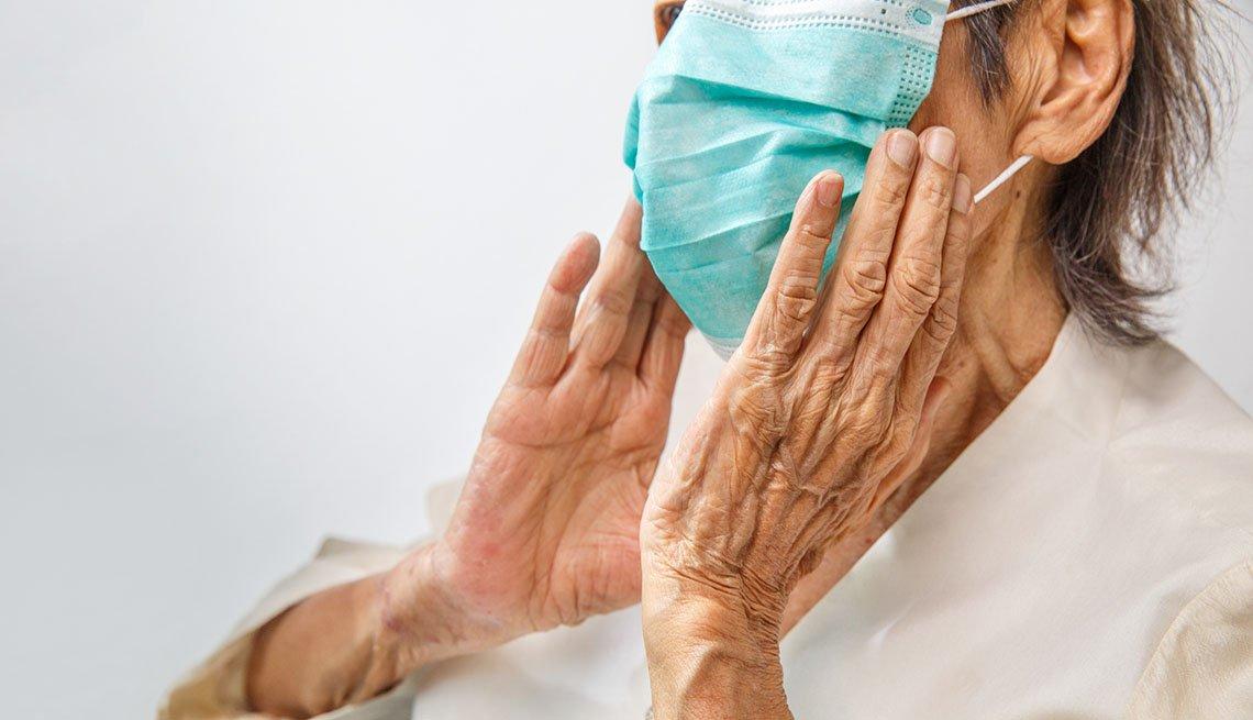 Anciana sosteniendo una máscara