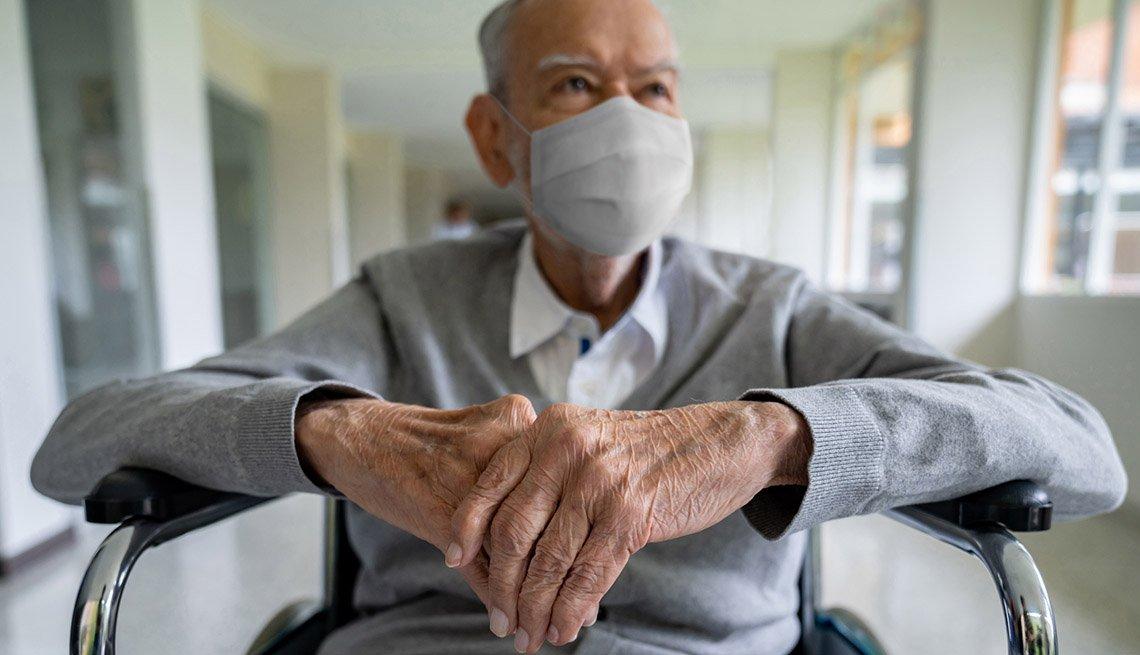 Hombre mayor con máscara en silla de ruedas