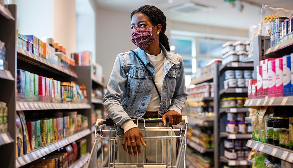 Una mujer de compras en un supermercado y usa una mascarilla