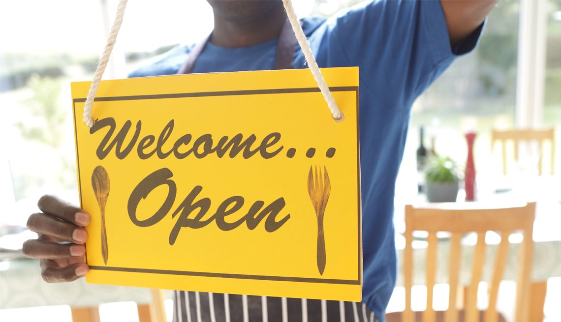 a worker in an apron turning a sign in the window to say welcome open
