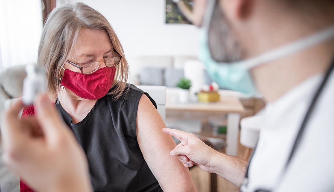 Médico explica como funciona la vacuna de refuerzo de covid a una mujer