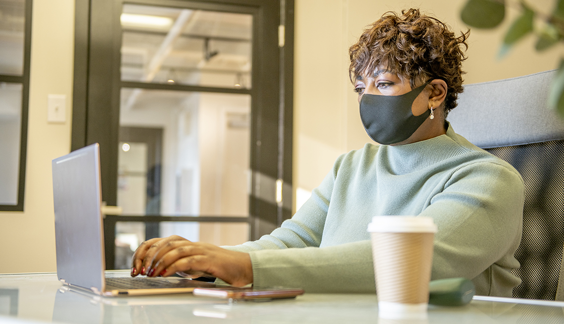 Una mujer trabaja en una oficina con su mascarilla puesta