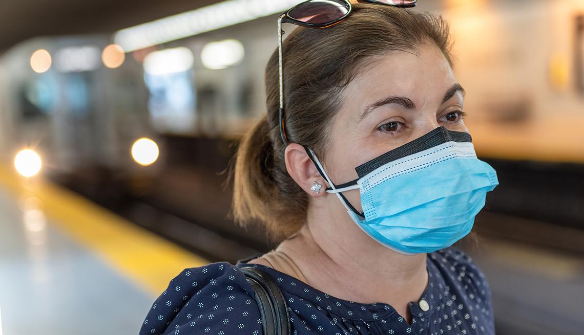 Una mujer con dos mascarillas en la estación del metro.