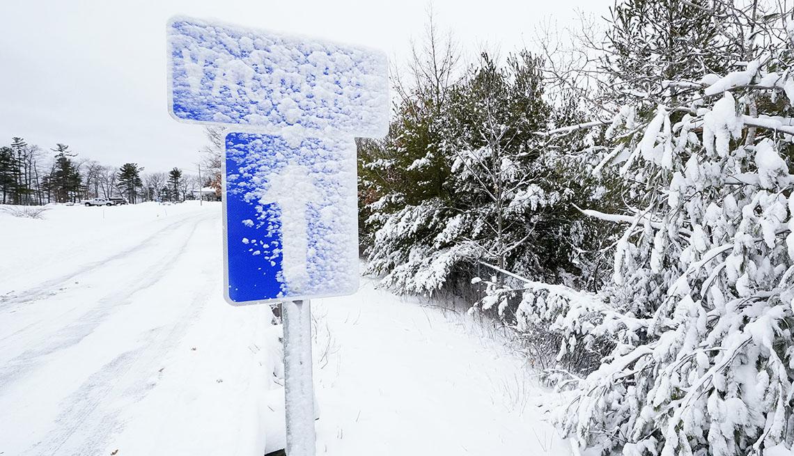 Letrero y calle cubierto de nieve