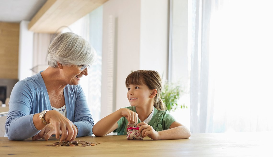 Older woman and granddaughter filling change jar