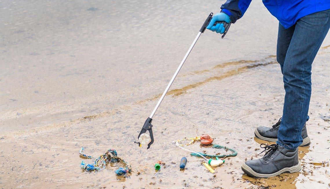 Man picking up litter off a beach