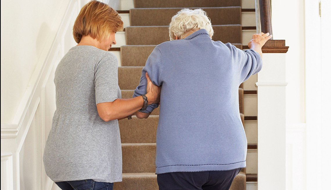 Woman helping an older woman up the stairs in her home