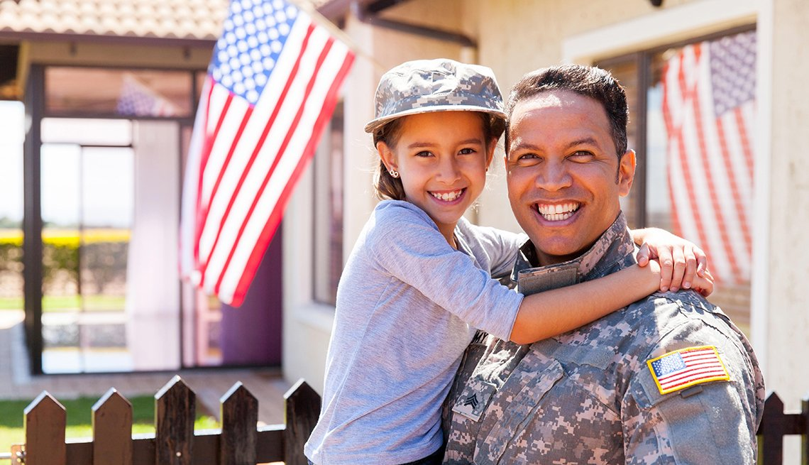 Portrait of us army soldier and little daughter outside their home