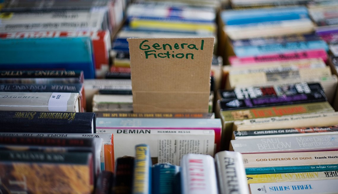 General fiction books for sale at an outdoor used book sale.