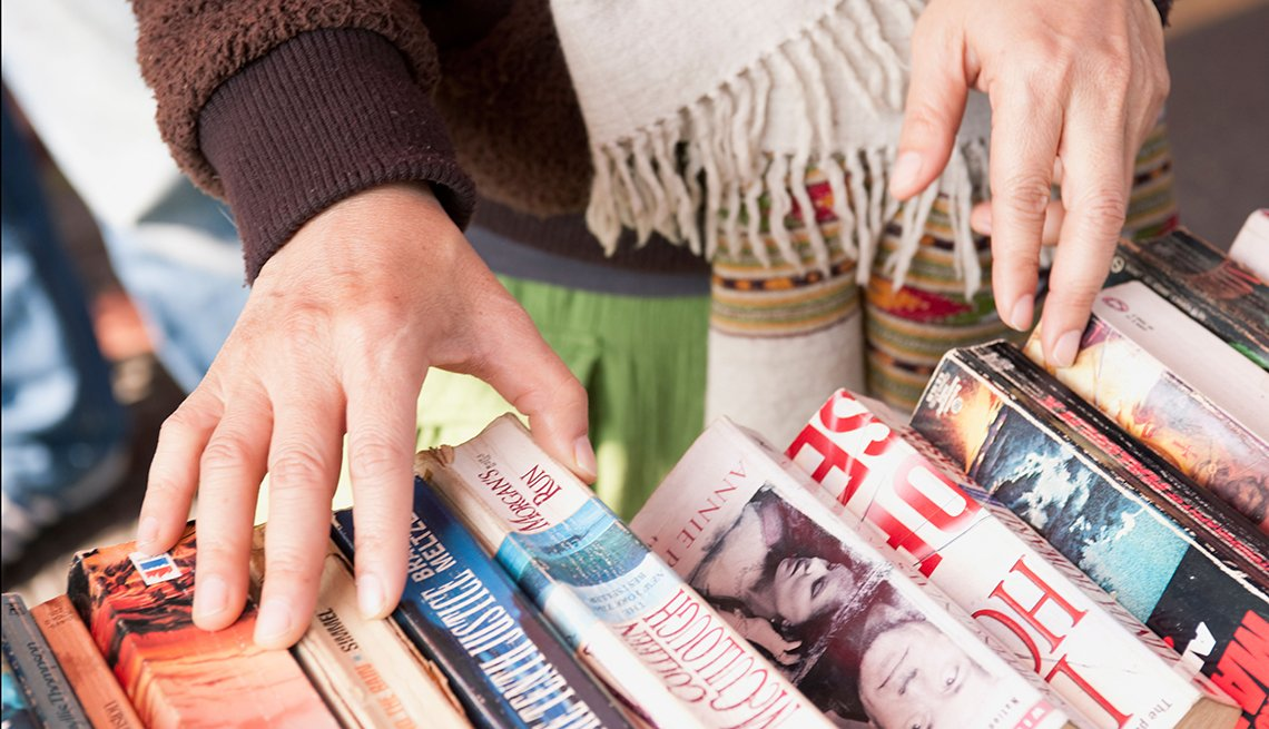 Close Up View Of A Persons Hands Looking Through Used Books