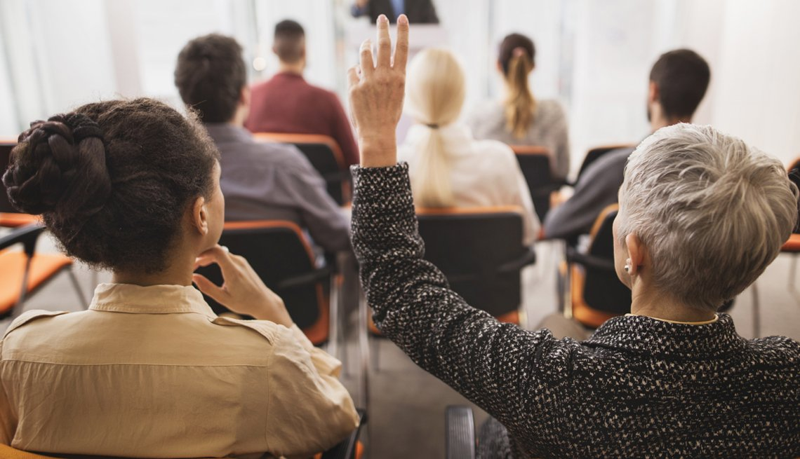 Woman asking a question in a classroom setting