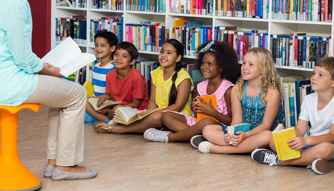 Woman with smiling children in library